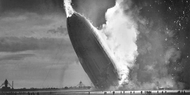 In this May 6, 1937 file photo, the German dirigible Hindenburg crashes to earth in flames after exploding at the U.S. Naval Station in Lakehurst, N.J. Werner Gustav Doehner, the last survivor of the disaster, died Nov. 8, 2019 at age 90 in Laconia, N.H. Doehner was 8 years old when he boarded the zeppelin in Germany with his parents and older siblings to return from a vacation. (AP Photo/Murray Becker, File)