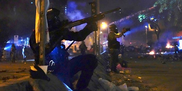 Police in riot gear prepare to fire as they move into the campus of Hong Kong Polytechnic University in Hong Kong.