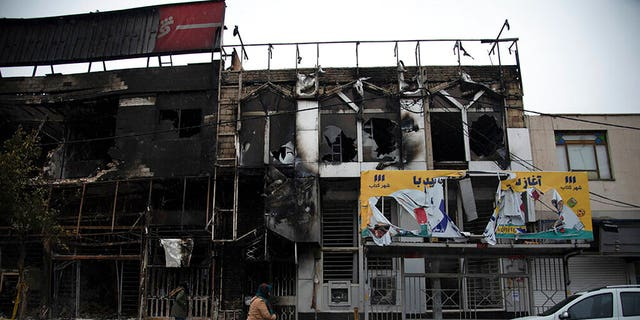 People walk past buildings that burned during protests that followed the Iran's decision to raise gasoline prices.