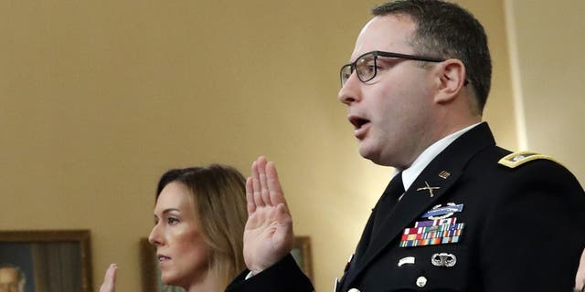 Jennifer Williams, an aide to Vice President Mike Pence, and National Security Council aide Lt. Col. Alexander Vindman, are sworn in before they testify before the House Intelligence Committee on Capitol Hill in Washington, Tuesday, Nov. 19, 2019, during a public impeachment hearing of President Donald Trump's efforts to tie U.S. aid for Ukraine to investigations of his political opponents. (AP Photo/Alex Brandon)