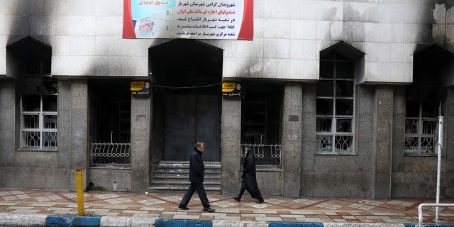 People walk past a bank that was burned during recent protests, in Shahriar, Iran, some 40 kilometers (25 miles) southwest of the capital, Tehran, Wednesday, Nov. 20, 2019. Protests over government-set gasoline prices rising struck at least 100 cities and towns, spiraling into violence that saw banks, stores and police stations attacked and burned.
