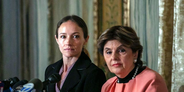 Teala Davies, left, and attorney Gloria Allred, right, at a news conference about the filing of a lawsuit against the estate of Jeffrey Epstein. Davies said she was 17 when he victimized her. (AP Photo/Jeenah Moon)