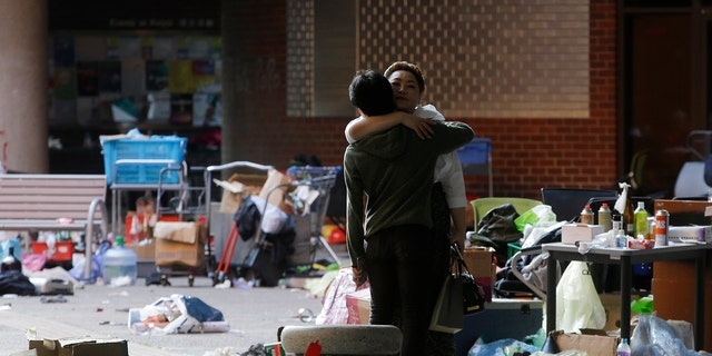 A protester hugs a social worker inside the campus of Hong Kong Polytechnic University in Hong Kong Friday, Nov. 22, 2019. Most of the protesters who took over the university last week have left, but an unknown number have remained inside for days, hoping somehow to avoid arrest. (AP Photo/Achmad Ibrahim)