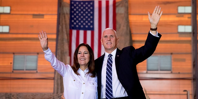 FILE - Vice President Mike Pence and his wife Karen Pence wave as they take the stage to speak to troops at Al Asad Air Base, Iraq, Saturday, Nov. 23, 2019. (AP Photo/Andrew Harnik)