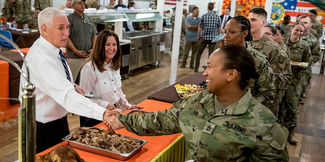 Vice President Mike Pence and his wife Karen Pence, second from left, serve turkey to troops at Al Asad Air Base, Iraq, Saturday, Nov. 23, 2019. (AP Photo/Andrew Harnik)
