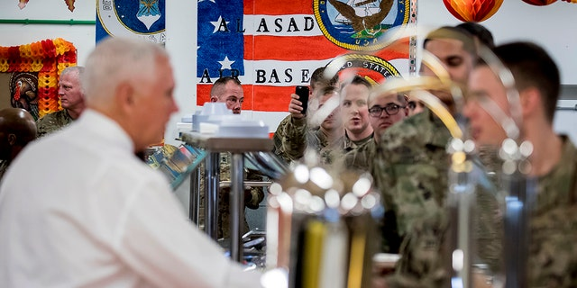 Vice President Mike Pence, foreground left, serves turkey to troops at Al Asad Air Base, Iraq, Saturday, Nov. 23, 2019. (AP Photo/Andrew Harnik)