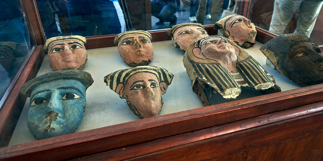 Wooden and clay mummies masks are displayed in Saqqara, south Giza, Egypt. Saturday, Nov. 23, 2019. The new discovery was displayed at a makeshift exhibition at the famed Step Pyramid of Djoser in Saqqara, south of Cairo, near the mummies and other artifacts were found in a vast necropolis. (AP Photo/Hamada Elrasam)