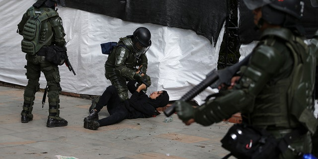 Riot police detain an anti-government protester in Bogota, Colombia, Saturday, Nov. 23, 2019. Authorities in Colombia are maintaining heightened police and military presence in the nation's capital following two days of unrest. (AP Photo/Ivan Valencia)