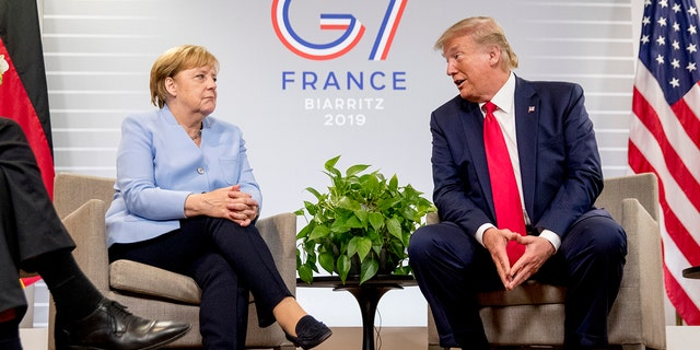 FILE - In this Monday, Aug. 26, 2019 file photo, U.S. President Donald Trump, accompanied by German Chancellor Angela Merkel, left, speaks during a bilateral meeting at the G-7 summit in Biarritz, France. A new study of the Pew Research Center and the Koerber-Stiftung foundation shows Germans and Americans continue to have notably different perspectives on the relationship between their two countries: Americans are much more optimistic about bilateral ties than Germans. (AP Photo/Andrew Harnik, File)