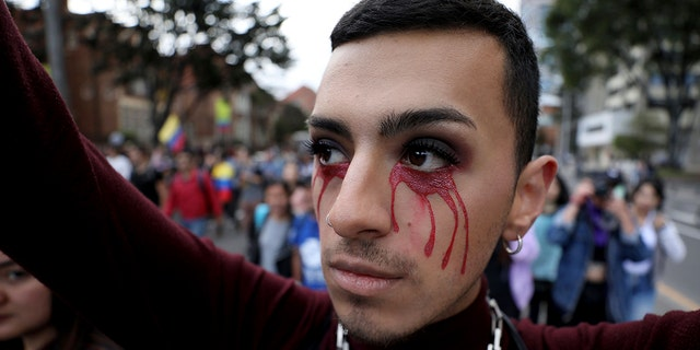 An anti-government demonstrator with red tears painted on his face joins protest in Bogota, Colombia, Monday, Nov. 25, 2019. (AP Photo/Fernando Vergara)