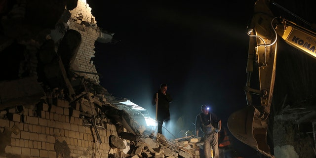 Rescuers search a collapsed building after a magnitude 6.4 earthquake in Thumane, western Albania, Tuesday, Nov. 26, 2019. Rescue crews with excavators searched for survivors trapped in toppled apartment buildings and hotels Tuesday after a powerful pre-dawn earthquake in Albania killed at least 18 people and injured more than 600. (AP Photo/Visar Kryeziu)