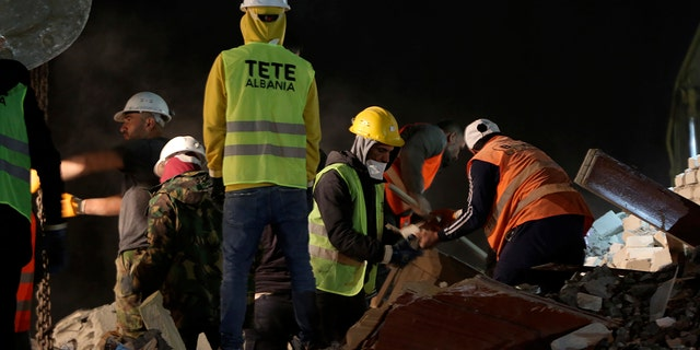 Rescuers search at a collapsed building after a magnitude 6.4 earthquake in Thumane, western Albania, Tuesday, Nov. 26, 2019. Rescue crews with excavators searched for survivors trapped in toppled apartment buildings and hotels Tuesday after a powerful pre-dawn earthquake in Albania killed at least 18 people and injured more than 600. (AP Photo/Visar Kryeziu)
