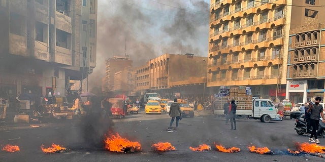 Political News: Anti-government protesters set fire to block streets during ongoing protests in Baghdad Wednesday. (AP Photo/Ali Abdul Hassan)