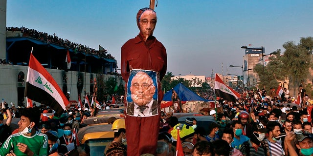 In this Wednesday, Oct. 30, 2019 file photo, anti-government protesters hold an effigy of Iraqi Prime Minister Adel Abdel-Mahdi during ongoing protests in Baghdad. Celebrations erupted in Iraq's Tahrir Square on Friday where anti-government protesters have been camped out for nearly two months following an announcement by Iraqi Prime Minister Adel Abdul-Mahdi, would be resigning. (AP Photo/Khalid Mohammed, File)
