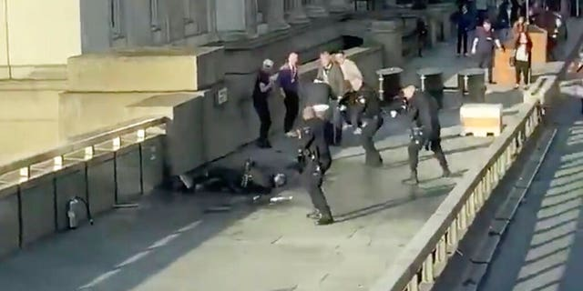 In a screenshot taken from video made available by @HLOBlog, a man is surrounded by police after an incident on London Bridge on Friday. (@HLOBlog via AP)