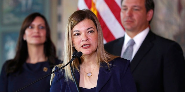 Barbara Lagoa, center, speaks as Gov. Ron DeSantis and Lt. Gov Jeanette Nunez, left, look on, Wednesday, Jan. 9, 2019, in Miami. (AP Photo/Wilfredo Lee)