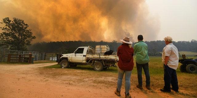 Locals watch smoke from a large bushfire outside Nana Glen, near Coffs Harbour, Tuesday, Nov. 12, 2019.