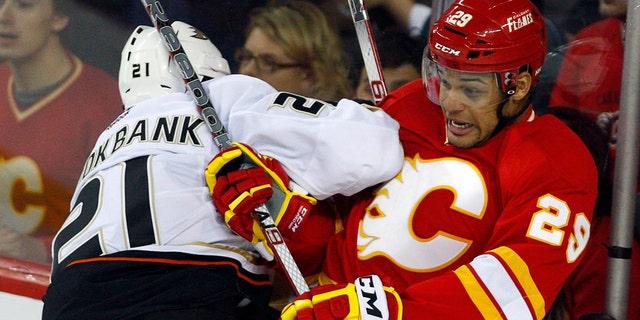 FILE - In this April 7, 2012, file photo, Anaheim Ducks' Sheldon Brookbank, left, checks Calgary Flames' Akim Aliu, a Nigerian-born Canadian, during third period NHL hockey action in Calgary, Alberta. (AP Photo/The Canadian Press, Jeff McIntosh, File)
