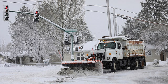 A city snowplow helps clear roads north of downtown Flagstaff Ariz. Friday Nov. 29 2019. A powerful storm making its way east from California is threatening major disruptions during the year's busiest travel weekend as forecasters warned that intensi