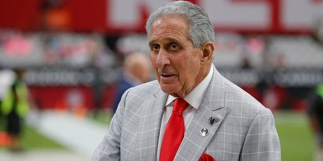 FILE - In this Oct. 13, 2019, file photo, Atlanta Falcons owner Arthur Blank stands on the field prior to an NFL football game against the Arizona Cardinals, in Glendale, Ariz. Blank is making his first major drive into international philanthropy. The Arthur M. Blank Family Foundation is expected to announce Thursday, Nov. 14, 2019, that it's donating $6.8 million to the group CARE. (AP Photo/Rick Scuteri, File)