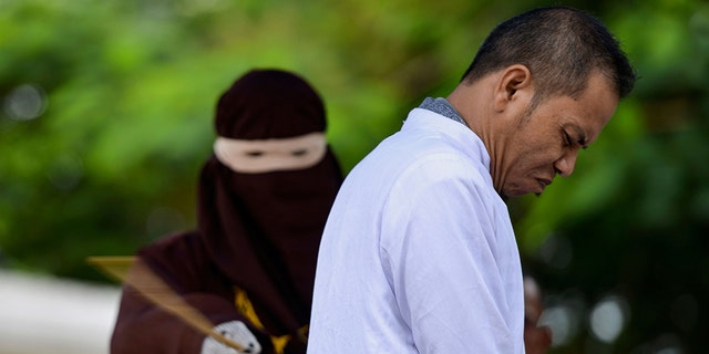 Aceh Ulema Council (MPU) member Mukhlis reacts as he is whipped in public by a member of the Sharia police in Banda Aceh on October 31, 2019.