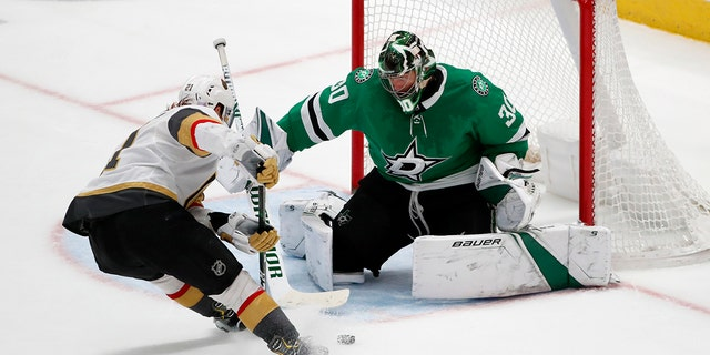 Dallas Stars goaltender Ben Bishop (30) makes a save against a shot from Vegas Golden Knights center Cody Eakin (21) in the third period of an NHL hockey game in Dallas, Monday, Nov. 25, 2019. (AP Photo/Tony Gutierrez)