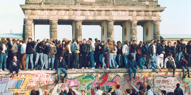 People standing on the Berlin Wall in front of the Brandenburg Gate in November 1989. (AP Photo, File)