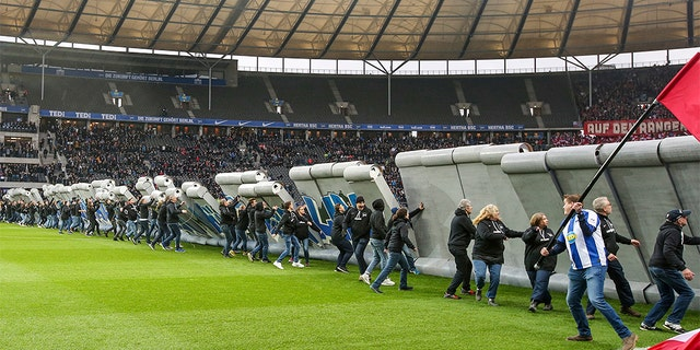 Fans tearing down the symbolic wall at the stadium in Berlin on Saturday. (Andreas Gora/dpa via AP)