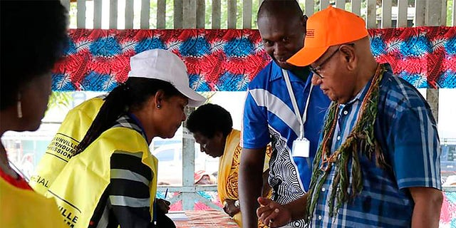 John Momis, right, president of the Autonomous Region of Bougainville, prepares to vote in Buka, Papua New Guinea, Saturday in a historic referendum to decide if they want to become the world's newest nation by gaining independence from Papua New Guinea. (Post Courier via AP)