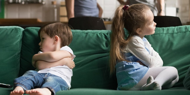 Upset offended toddler brother and sister sitting separately on couch, sofa with arms crossed, little girl and boy ignoring each other, not talking, puzzled parents discuss situation. (Photo: iStock)
