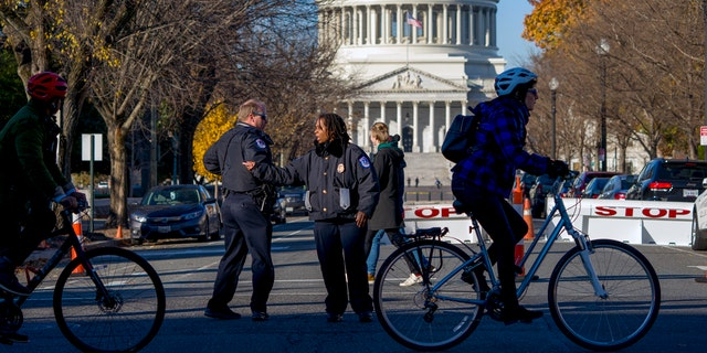 Officers direct passerby to keep at a safe distance from the U.S. Capitol Tuesday. (AP Photo/J. Scott Applewhite)