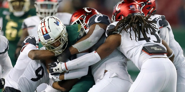 South Florida's Bryce Miller is wrapped up by Cincinnati defenders during the second half of an NCAA college football game, Saturday, Nov. 16, 2019, in Tampa, Fla. Cincinnati won 20-17. (AP Photo/Mike Carlson)