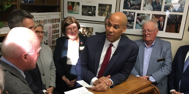 Democratic presidential candidate Sen. Cory Booker of New Jersey Statehouse hands over a $1,000 check to longtime New Hampshire Secretary of State Bill Gardner as he files place his name on the first-in-the-nation presidential primary, in Concord, NH on Nov. 15, 2019