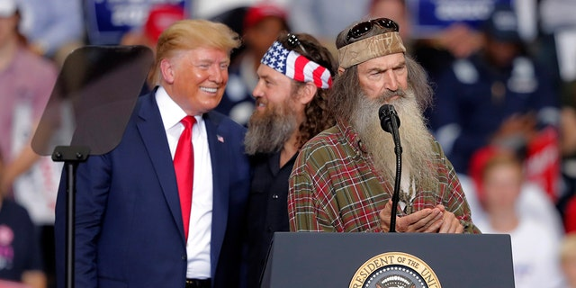 President Donald laughs with Willie Robertson, of the reality TV series Duck Dynasty, and Phil Roberston, the family patriarch, 对, at a campaign rally in Monroe, 的。, 星期三, 十一月. 6, 2019.
