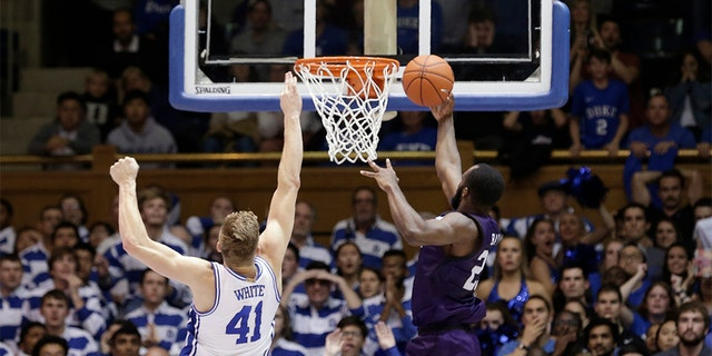 Stephen F. Austin forward Nathan Bain (23) made the game-winning basket over Duke forward Jack White (41) during overtime in an NCAA college basketball game on Tuesday. Stephen F. Austin won 85-83. (AP Photo/Gerry Broome)