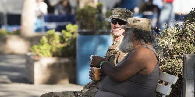Staff Sgt. Robert Gross sat with a homeless veteran during the Santa Barbara Stand Down. (U.S. Air Force photo by Airman 1st Class Hanah Abercrombie)