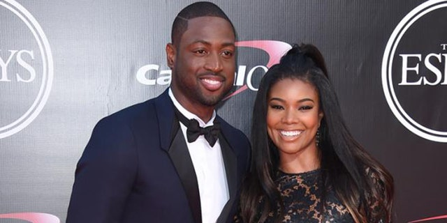 Gabrielle Union and husband Dwyane Wade pose for cameras.
