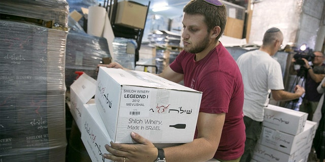 A worker carries boxes of wine bottles for export at Shiloh Wineries, north of Ramallah in this 2015 photo.