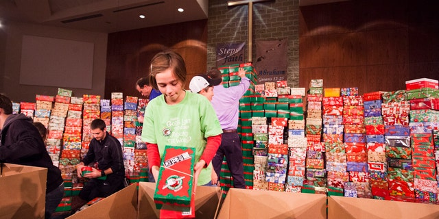 Evilyn Pinnow readies one of hundreds of Operation Christmas Child shoe box gifts to be processed and sent to children in more than 100 countries around the world.