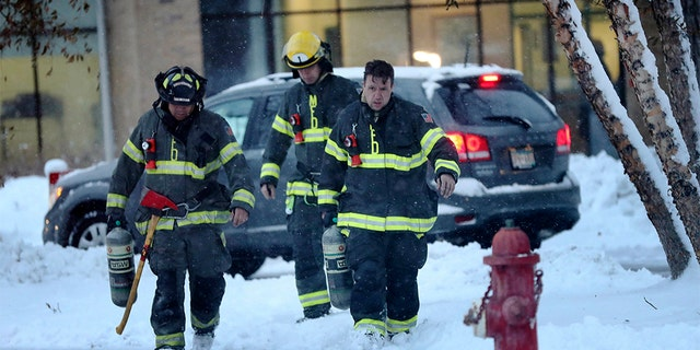 Minneapolis firefighters leave high-rise apartment building after a deadly fire Wednesday. (David Joles/Star Tribune via AP)