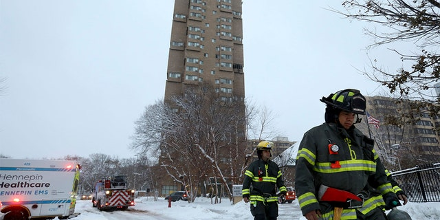 Minneapolis firefighters leave after a deadly fire at a high-rise apartment building, in background, Wednesday in Minneapolis. (David Joles/Star Tribune via AP)