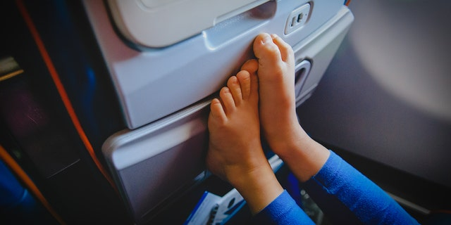 A woman's picture of an airline passenger putting their feet on her headrest leaves many online horrified and disgusted by the in-flight offense. (Photo: iStock)