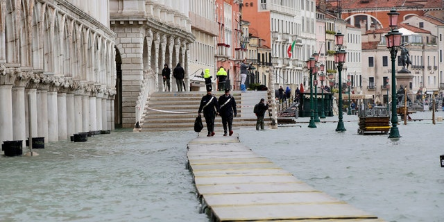 Two police officers walk on a gangway in flooded Venice, Italy, Sunday, Nov. 17, 2019.