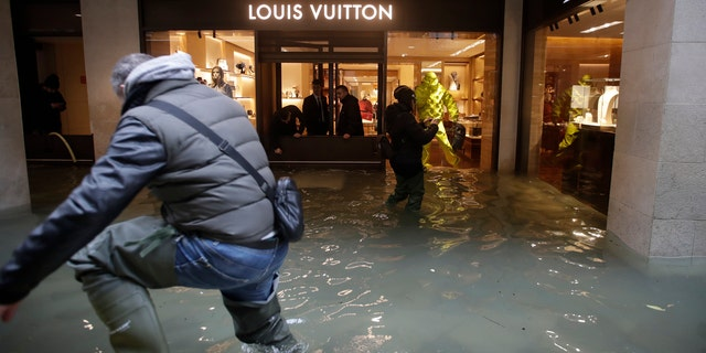Flood water reaches a luxury shop in Venice, Italy, Sunday, Nov. 17, 2019.