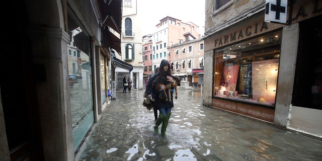A Venetian citizen carries her dog Nana as she walks in a flooded street of Venice, Italy on Sunday.