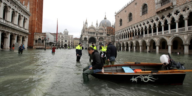 A man sits on a small boat in a flooded St.Mark square in Venice, Italy on Sunday.