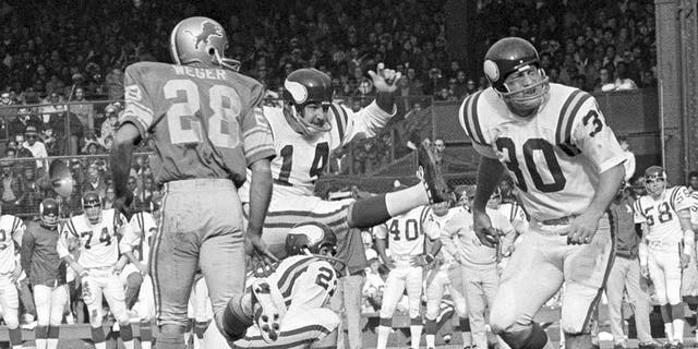 FILE - In this Sunday, Nov. 1, 1970 file photo, Minnesota Vikings Fred Cox (14) kicks a field goal from near the twenty-eight yard line on score three points in first quarter of an NFL football game against the Detroit Lions in Detroit. Fred Cox, the former Minnesota Vikings kicker who co-created the Nerf football, has died. He was 80. The Vikings announced Cox's death Thursday, Nov. 21, 2019. (AP Photo/File)