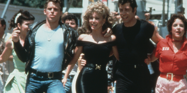 """Olivia Newton-John and John Travolta appear in """"Grease."""" Newton-John's iconic tight pants and top from her """"Bad Sandy"""" transformation went on auction for big bucks."""