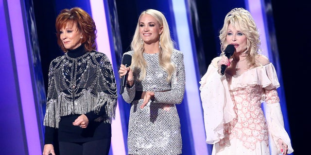 NASHVILLE, TENNESSEE - NOVEMBER 13: (FOR EDITORIAL USE ONLY) (L-R) Reba McEntire, Carrie Underwood and Dolly Parton speak onstage during the 53rd annual CMA Awards at the Music City Center on November 13, 2019 in Nashville, Tennessee. (Photo by Terry Wyatt/Getty Images,)