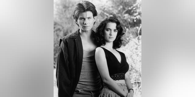 """Christian Slater and Winona Ryder standing together in a scene from the film """"Heathers,"""" 1988."""